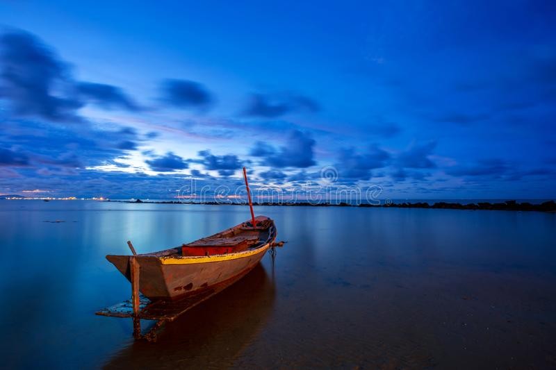 Fishing boat in perfectly calm sea water like glass with the clouds in the sky, long Exposure taken during sunrise. Fishing boat in perfectly calm sea water like stock photography