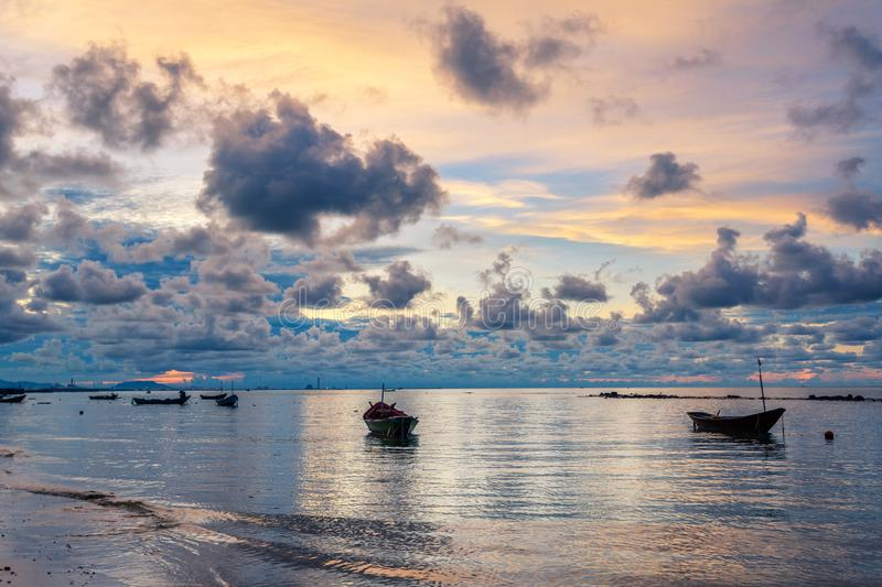Fishing boat in perfectly calm sea water like glass with the clouds in the sky, long Exposure taken during sunrise. Fishing boat in perfectly calm sea water like stock image