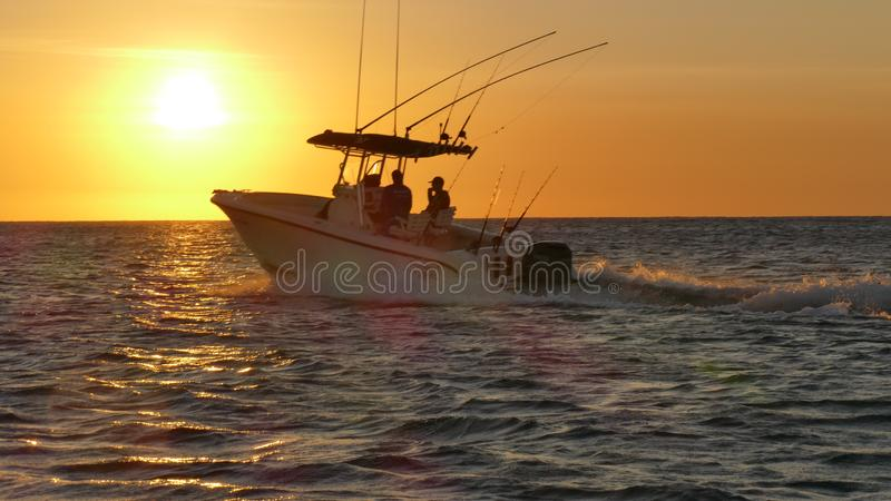 Fishing boat racing out to sea in Mexican waters. stock photos