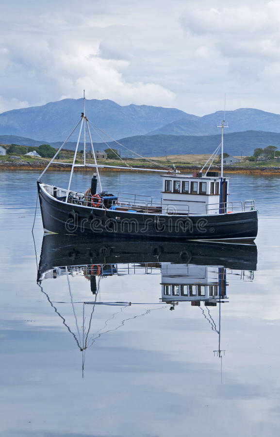 Fishing boat reflected in the water royalty free stock image