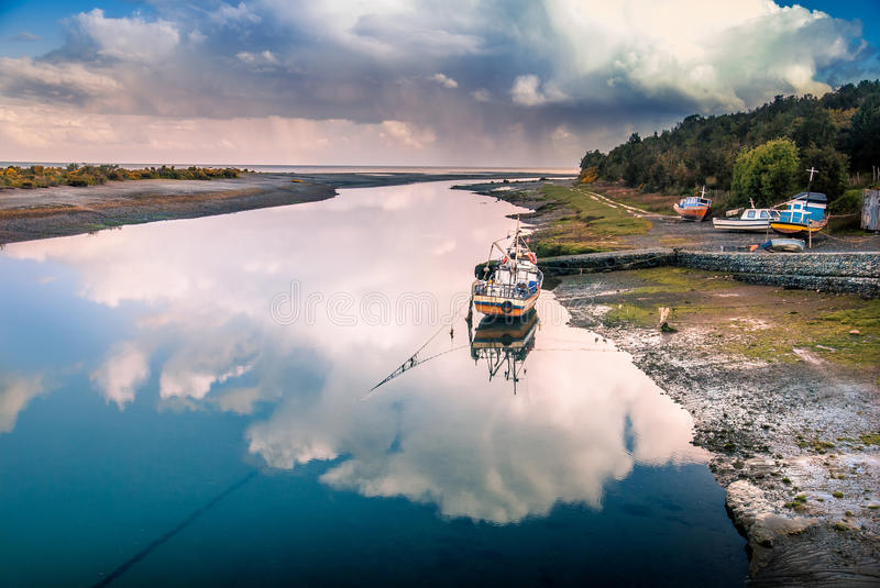 Fishing boat in the reflection of the cloud on the river by the ocean, Aytuy, Chiloe island, Chile, South America royalty free stock photography