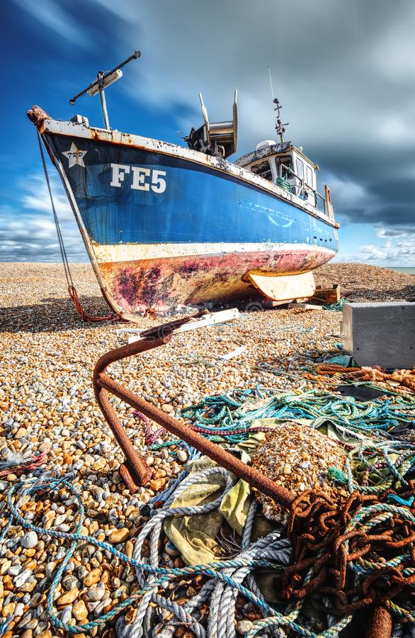 Fishing boat resting on a shingle beach. Long exposure. A rusting anchor in the foreground, still with it`s chain attached, leads to a fishing boat resting on stock photo