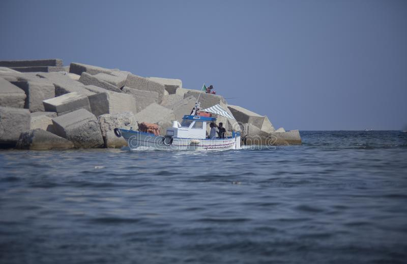 Fishing boat returns to the port stock photography