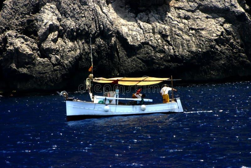 Fishing boat and rocky coast royalty free stock photos
