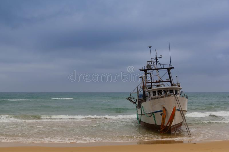 Fishing boat run aground on the beach stock photos