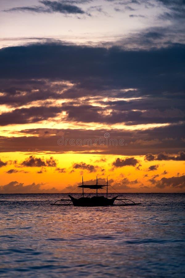 Fishing boat sailing along sunset royalty free stock images