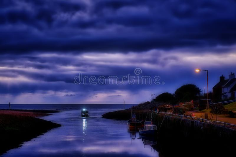 Fishing boat sailing from Brora Harbour. At dawn with reflections in the still waters of the incoming tide stock image
