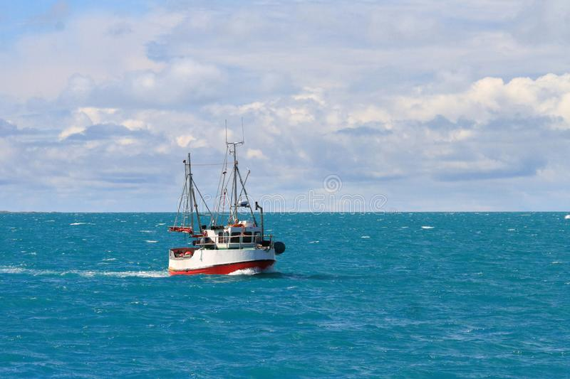 Fishing boat sailing in the sea of Vestfjord. Dividing Lofoten Islands from mainland Norway stock image