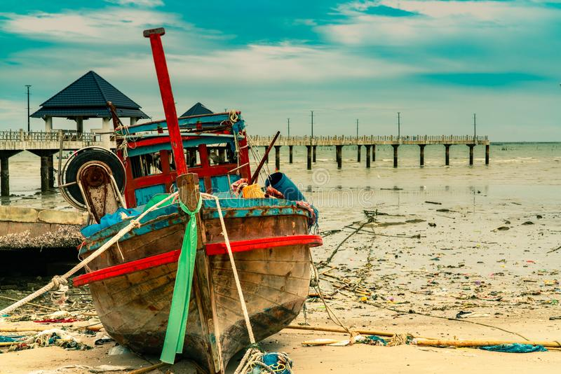 Fishing boat on sand beach near the bridge and sea. Relaxation on paradise tropical beach and resort concept. Garbage on beach royalty free stock photos