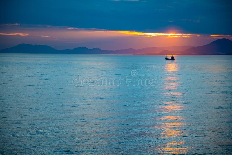 Fishing boat on sea in sunset lights in Sanya, Hainan, China stock photos