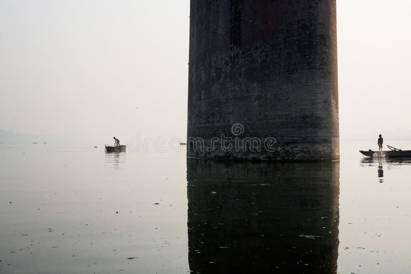 Fishing boat silhouette with Mawlamyine Malviya Bridge background. India royalty free stock photos