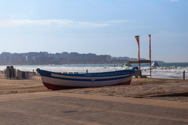 Fishing boat standing on a sandy beach, against the sea and the city in the distance. royalty free stock images