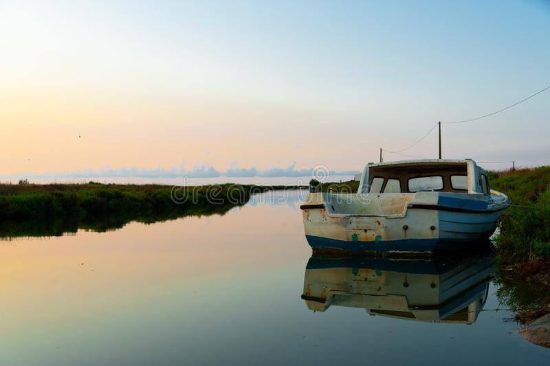 Lonely abandoned fishing boat at sunrise in ebro delta park in catalunya, a quiet scene symbol of loneliness and peace of mind. Fishing boat at sunrise in ebro royalty free stock photo