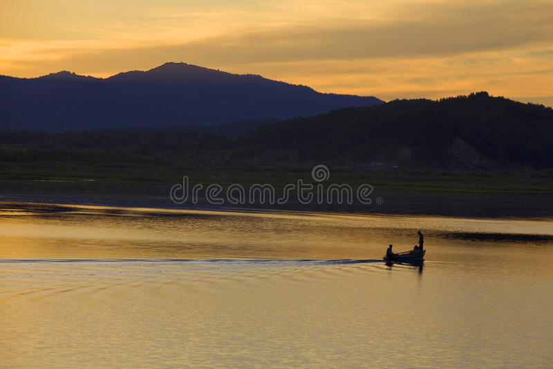 Fishing boat on sunset lake royalty free stock photos