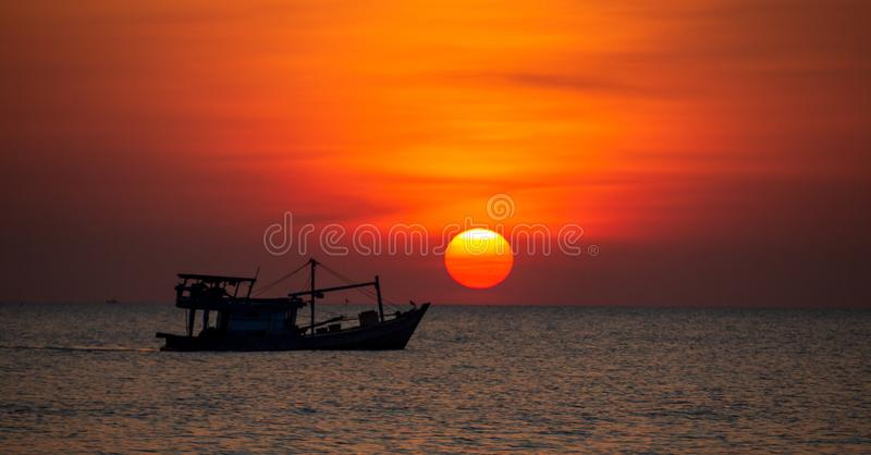 Fishing Boat at Sunset in Vietname. A huge orange yellow sun silhouettes at fishing trawler in the sea off Phu Quoc Island in Vietnam royalty free stock photo