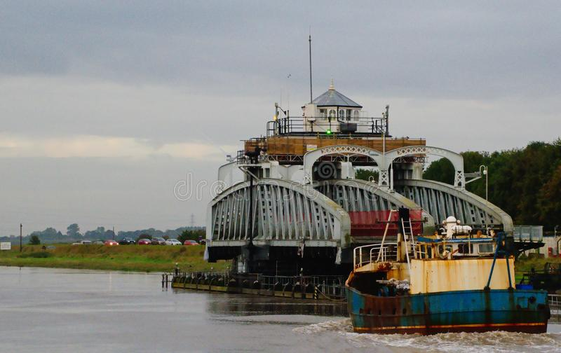 Fishing boat about to pass through the swing bridge royalty free stock photo