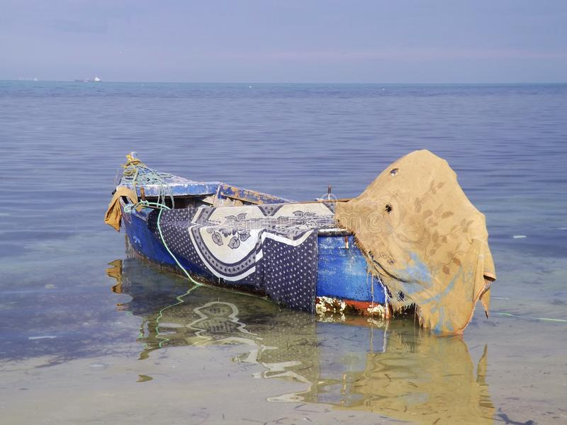 Fishing boat in Tunisia, Cap Bon, North coast. A fisherman has protected his boat with colored blankets stock images