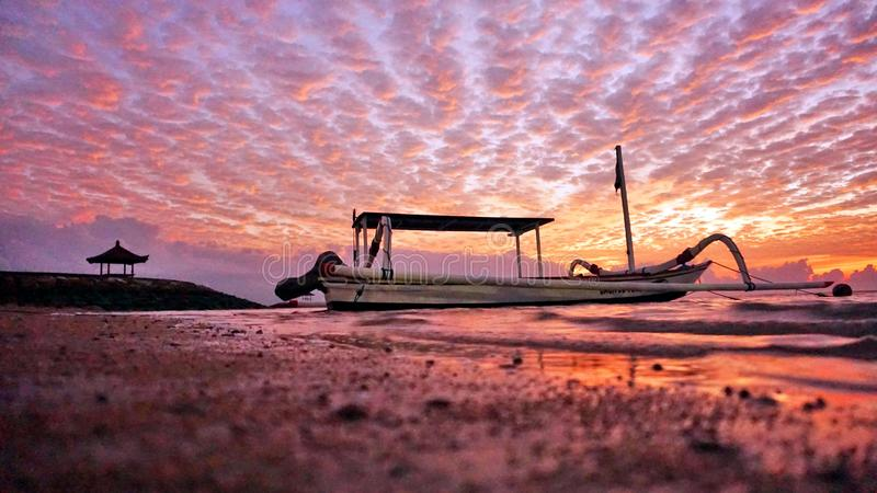 Fishing boat under dramatic sunrise sky view in very low angle. Beach nature landscape scenery with beautiful colorful morning sky stock images