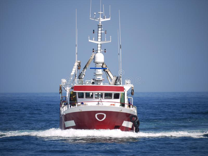 Fishing Boat Underway at Speed. To harbour to discharge fish stock photo
