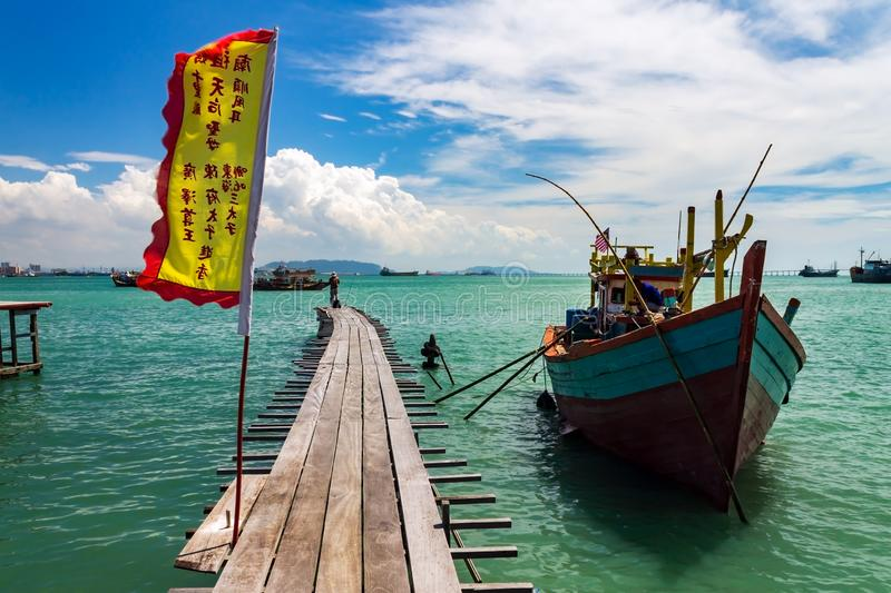 Fishing boat by a wooden bridge with a chinese flag in Tan Jetty, Clan Jetties, Georgetown, Penang, Malaysia stock photo