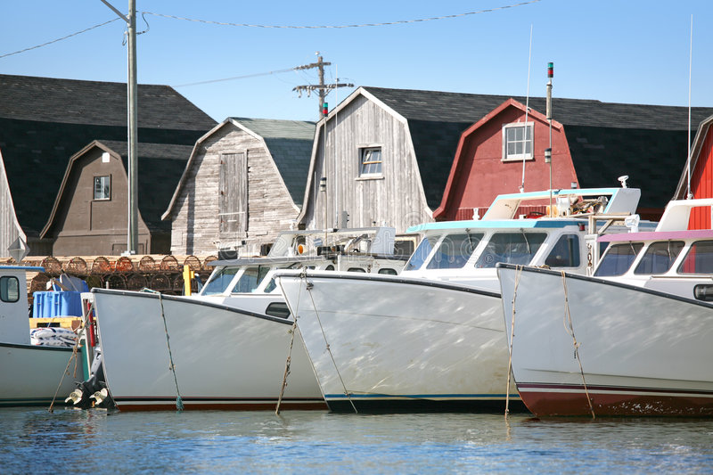 Fishing Boats. Lobster fishing boats, traps and bait sheds at a small harbour wharf on Prince Edward Island, Canada stock photography