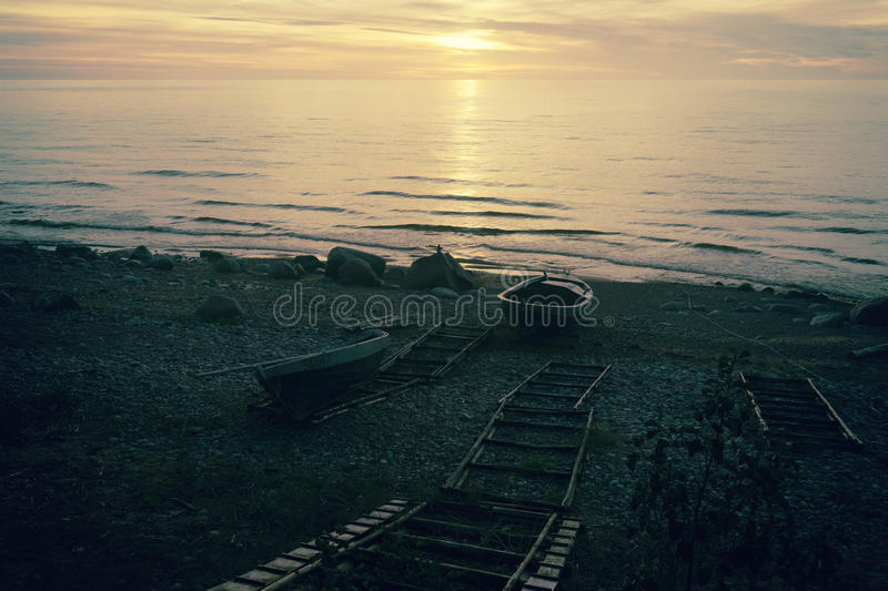 Fishing boats on the beach at sunset royalty free stock photos