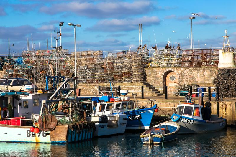 Fishing Boats and cages at Brixham Harbor, English Seaside. Fishing equipment pots and cages above on stone built pier above boats sitting out at brixham harbour royalty free stock photos