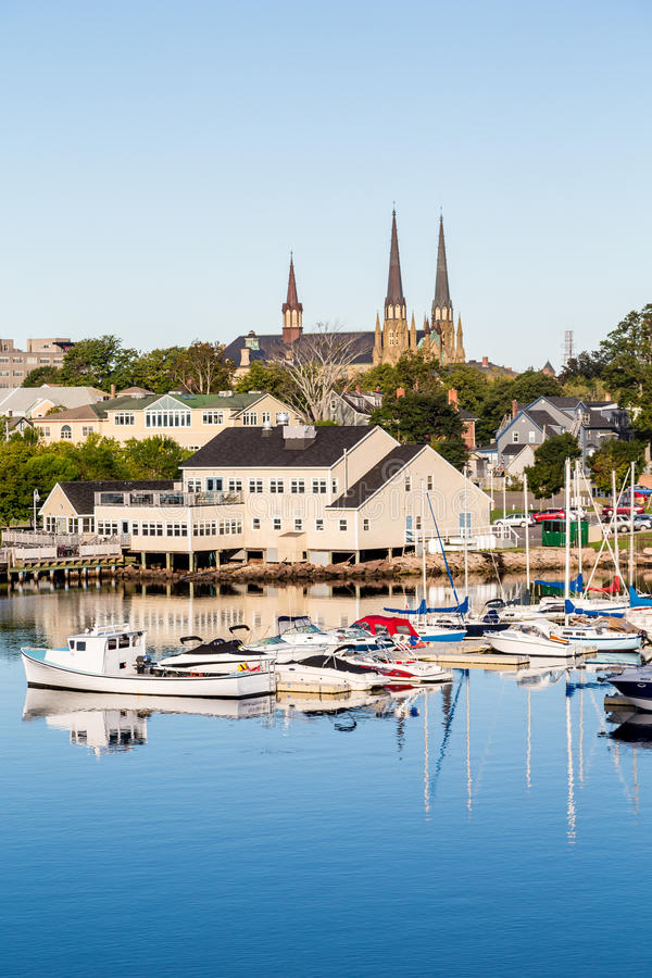 Fishing Boats and Church in Charlottetown. Small fishing boats in a calm blue harbor on Prince Edward Island in Canada stock image