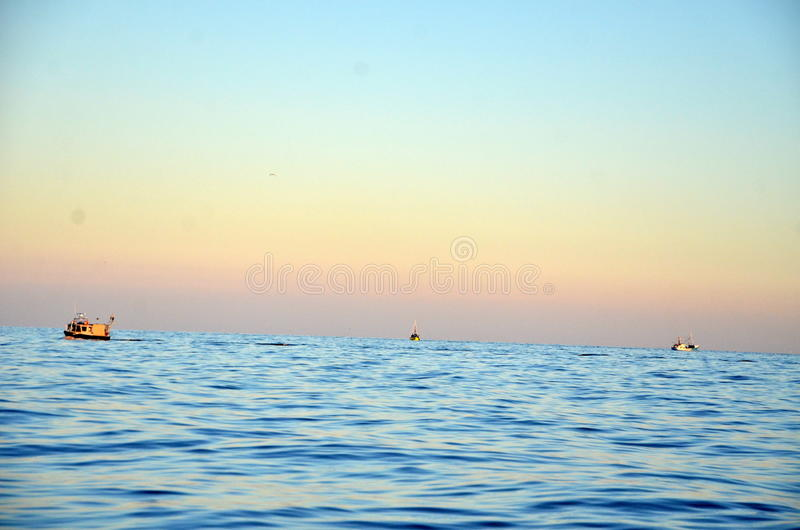Fishing boats depart in the morning, during sunrise, in the sea. Fishing boats depart in the morning, during sunrise, in the Baltic Sea royalty free stock image