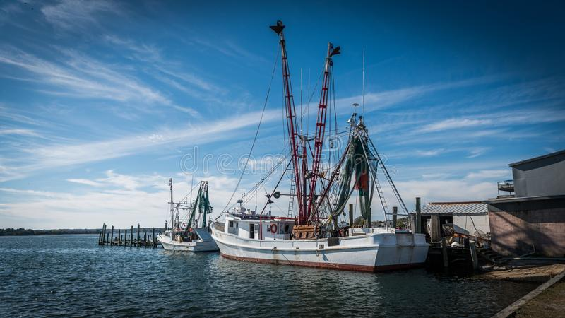 Fishing boats at dock with nets stock image
