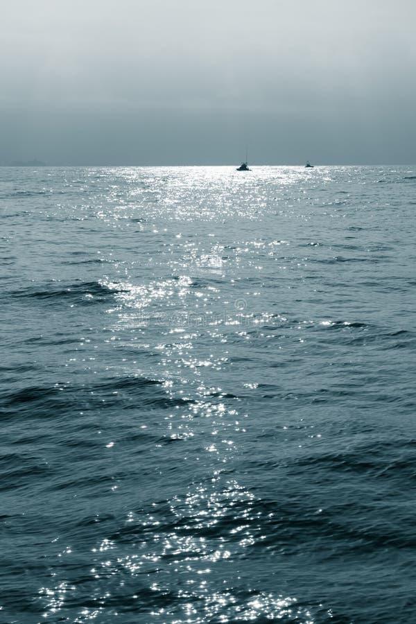 Fishing boats at dusk on ocean stock photo