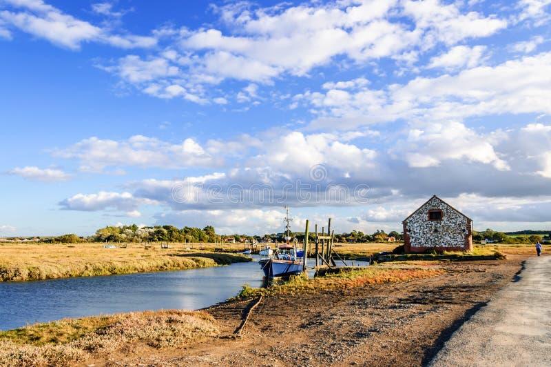 Fishing boats moored on coastal river in marshland, East Anglia, England, United Kingdom. Thornham, Norfolk, England, United Kingdom - October 12, 2012: Fishing stock image
