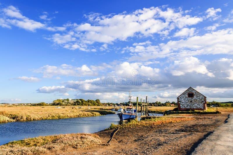 Fishing boats moored on coastal river in marshland, East Anglia, England, United Kingdom. Thornham, Norfolk, England, United Kingdom - October 12, 2012: Fishing royalty free stock photos