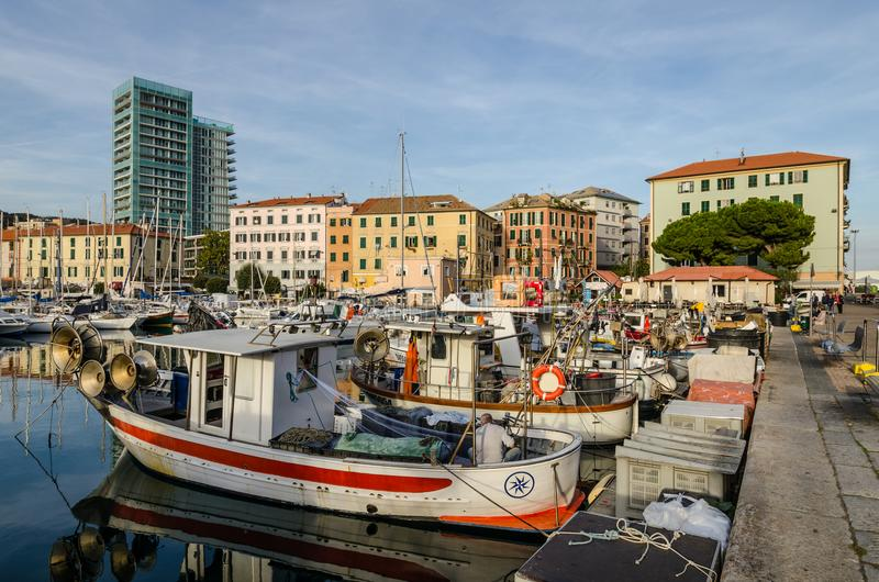 Fishing boats at the old dock of Savona in Liguria. Fishing boats moored at the old dock, in the background the ancient and modern buildings, Savona in Liguria stock photos