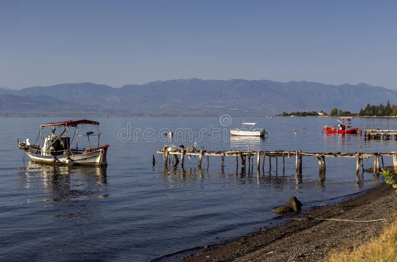 The fishing boats is moored near the shore and wooden, old pier close-up Greece stock photos