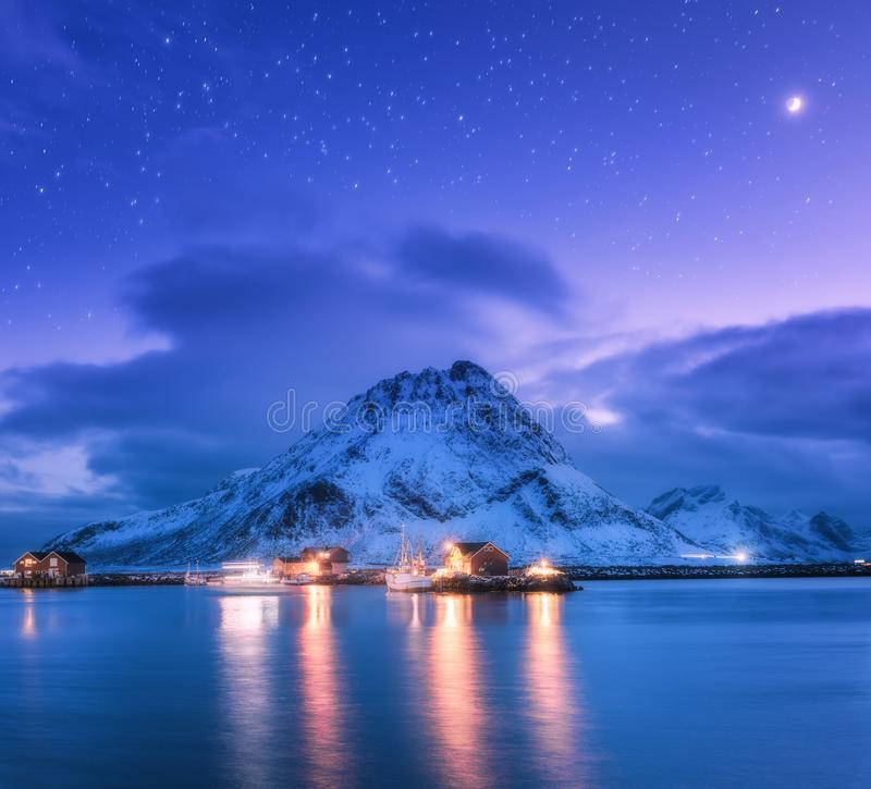 Fishing boats near pier on the sea and snowy mountains at night. Fishing boats near pier on the sea against snowy mountains and starry purple sky with moon at royalty free stock images