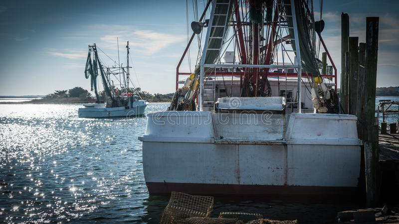 Fishing boats at dock with nets stock photography