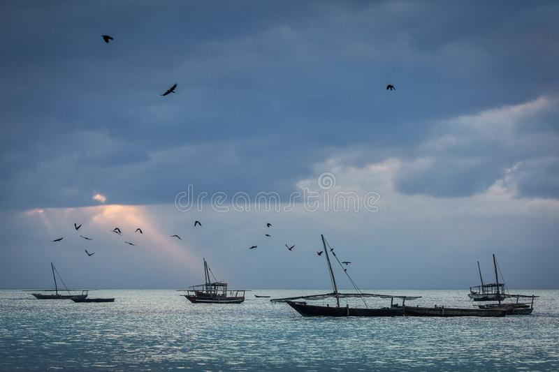 Fishing boats in ocean with birds and storm clouds in background. Zanzibar, Tanzania stock images