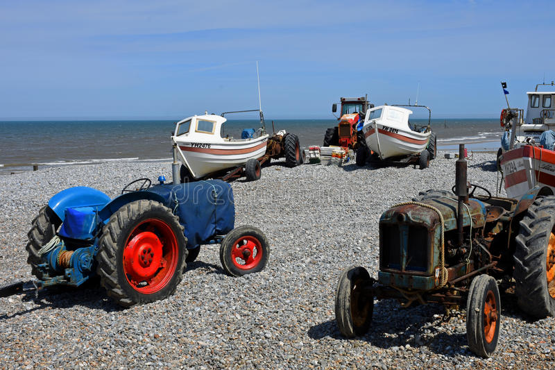 Fishing Boats and Old Tractors, Cromer, Norfolk, England. Fishing boats and old tractors on Cromer Beach, Norfolk, England royalty free stock images