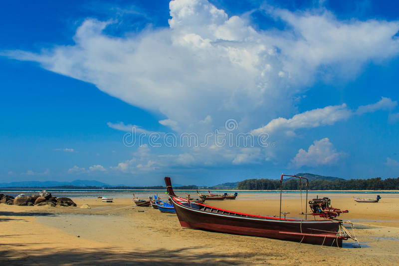 Fishing boats parking on the beach with blue sky background in t. He cloudy day stock image