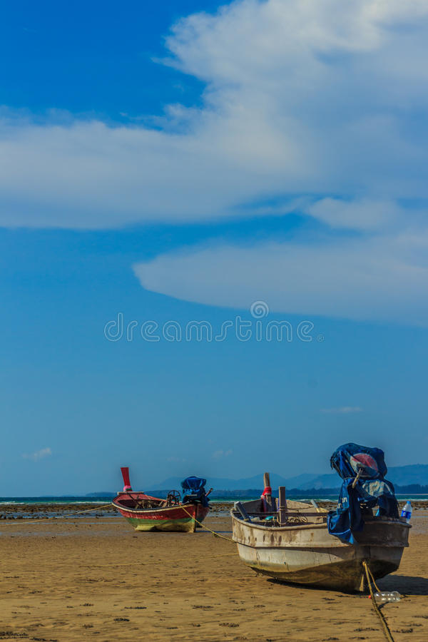 Fishing boats parking on the beach with blue sky background in t. He cloudy day stock images