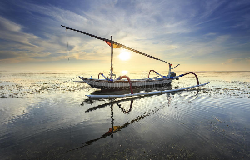 Fishing boats populate the shoreline at the Sanur Beach stock image