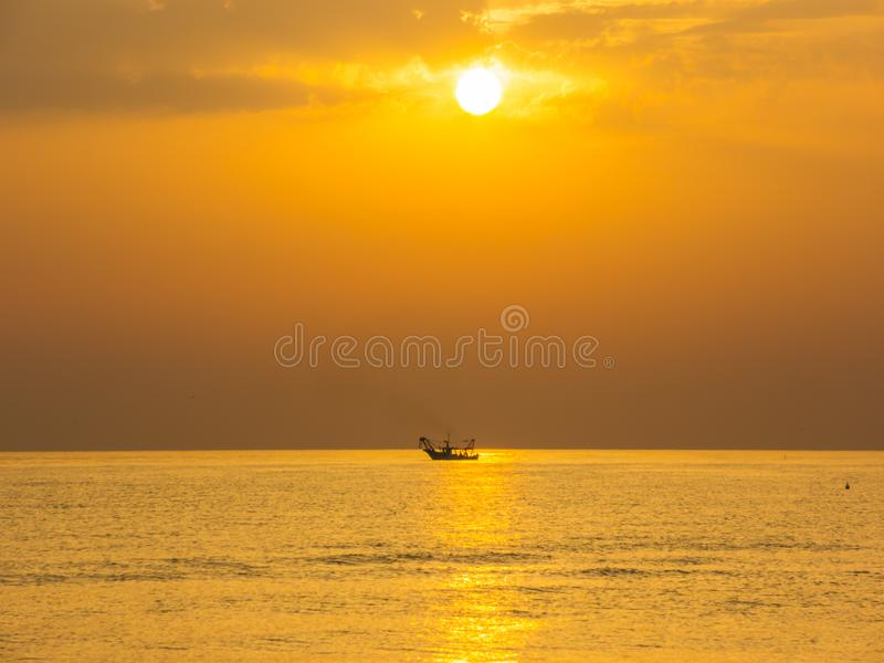 Fishing boats pull their nets at the sunrise. Adriatic cost. Emilia Romagna. Italy stock image