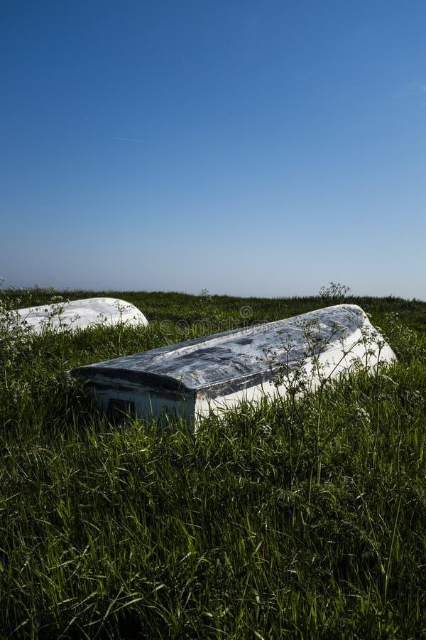 Fishing boats put upside down in a green field near a coast stock photos