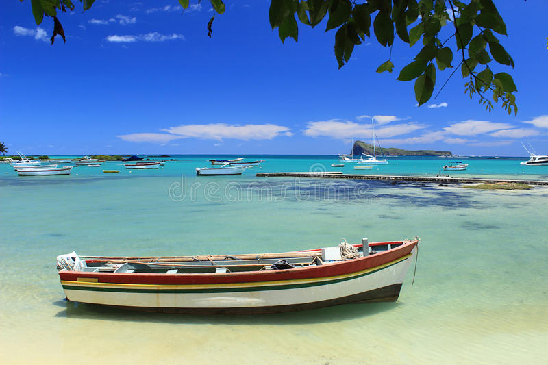 Fishing boats, turquoise sea and tropical blue sky. Images of a fishing boat at moor in clear shallow water in Cap Malheureux, a coastal village in the north of royalty free stock image