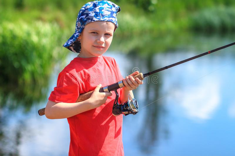 Fishing. Boy fisherman with fishing rod on lake. Portrait of child with spinning in hands on river background stock photos