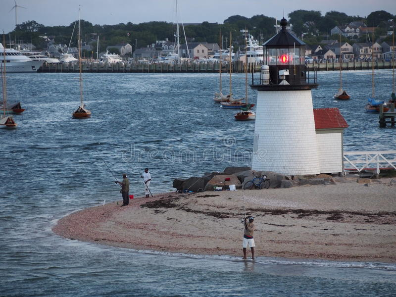 Fishing By the Brant Point Light. Tourist and Locals enjoy fishing by the Brant Point Lighthouse on Nantucket Island MA royalty free stock images