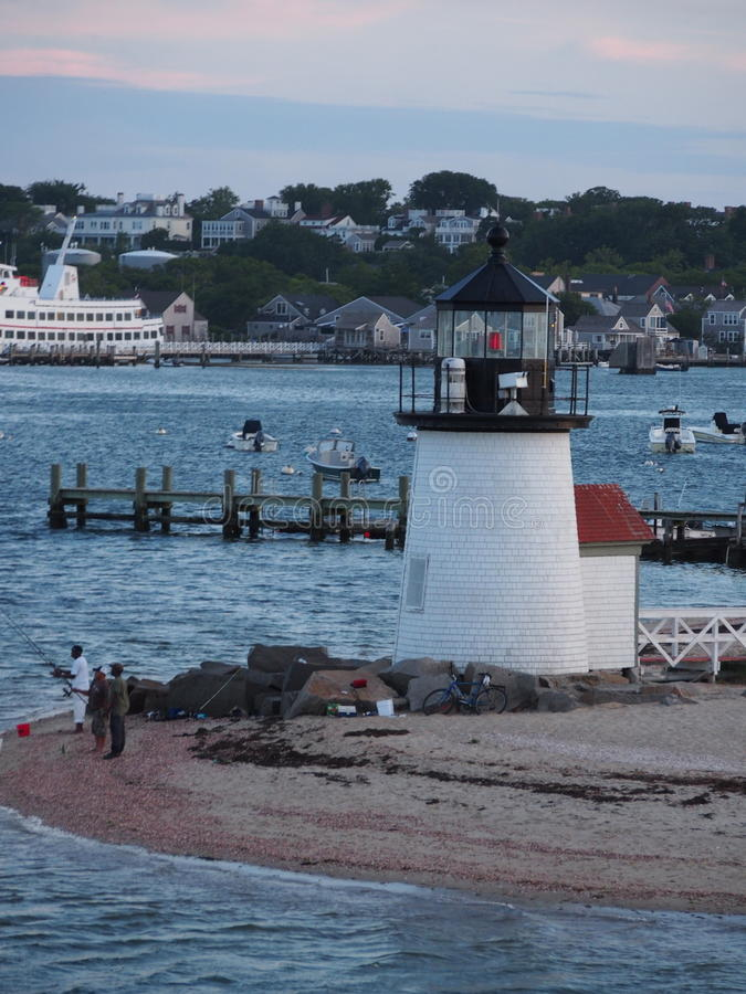 Fishing at the Brant Point Light. Tourist and Locals enjoy fishing by the Brant Point Lighthouse on Nantucket Island MA stock photo