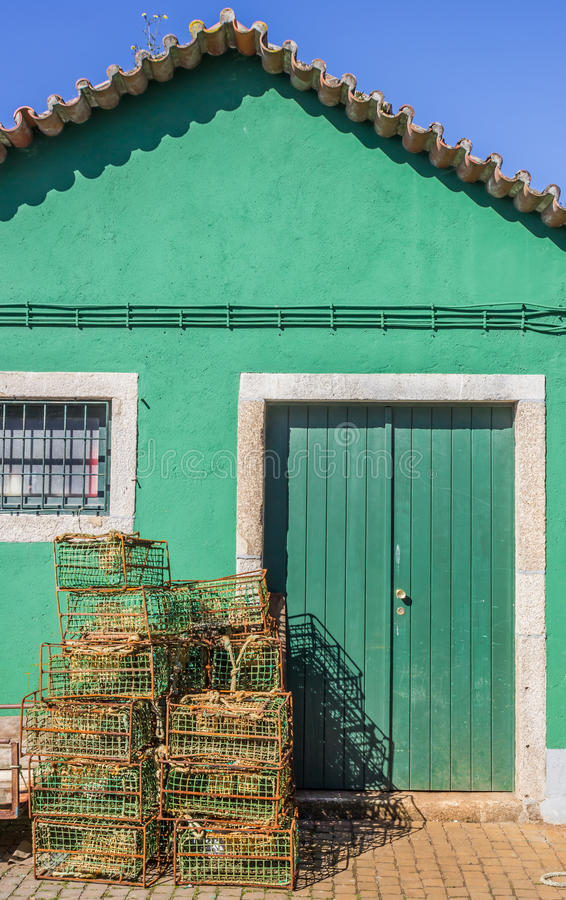 Fishing cages in front of a green building. In Viana do Castelo, Portugal royalty free stock photo