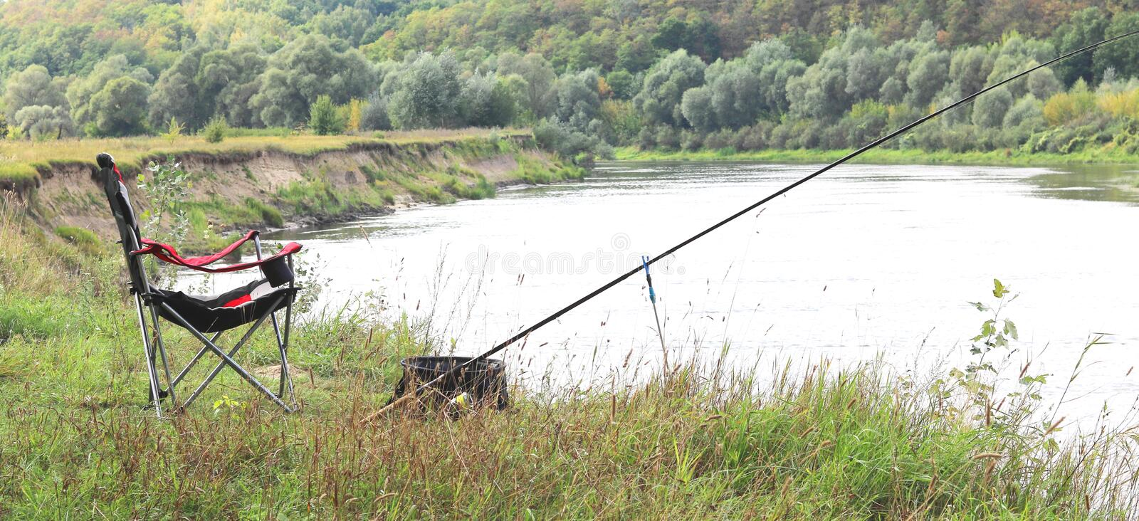 Fishing chair, rod and bait on the river bank. In autumn royalty free stock photography